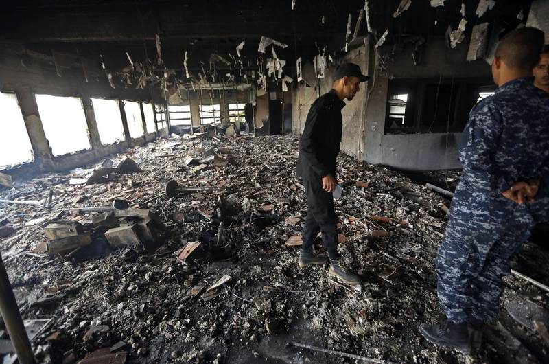Libyan police check the damage at the Libyan electoral commission headquarters in the capital Tripoli after it was targeted by suicide bombers on May 2, 2018. Suicide bombers stormed Libya's electoral commission in the Libyan capital, killing at least a dozen people in an attack claimed by the Islamic State jihadist group. / AFP PHOTO / MAHMUD TURKIA
