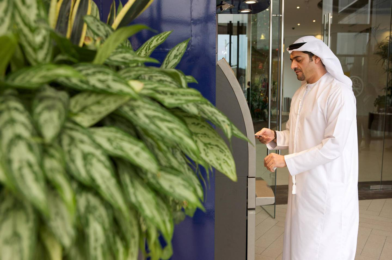 An arab man using an ATM Machine.