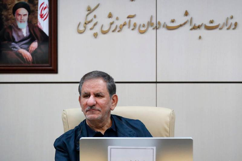 In this Feb. 28, 2020 photo, released by official website of the Office of the Iranian Vice-President, Senior Vice-President Eshaq Jahangiri sits in front of a painting of the late revolutionary founder Ayatollah Khomeini during a top-level meeting on prevention and combating the coronavirus, in Tehran, Iran. Jahangiri and two other Cabinet members have contracted the new coronavirus, semiofficial Fars News Agency reported Wednesday, March 11, 2020. The vast majority of people recover from the new virus. (Office of the Iranian Vice President via AP)