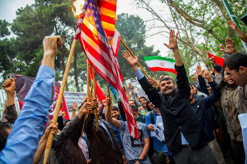 Iranians wave American and Iranian flags during an anti-U.S. demonstration outside the former U.S. embassy headquarters in Tehran, Iran, on Wednesday, May 9, 2018. U.S. President Donald Trump pulled out of the 2015 deal that put limits on Iran's nuclear program in exchange for rapprochement with the West. Photographer: Ali Mohammadi/Bloomberg