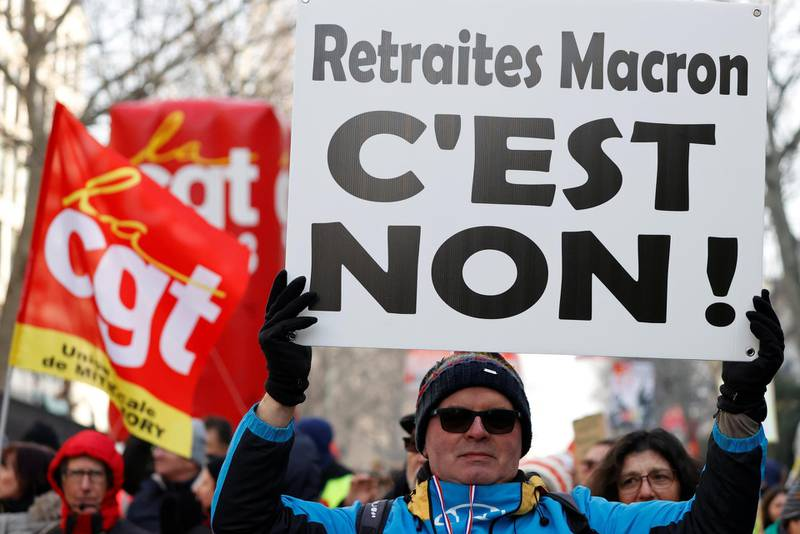 """A demonstrator holds a placard which reads """"No to Macron's pensions reform"""" during a demonstration against French government's pensions reform plans in Paris as part of another day of nationwide strikes and protests in France, January 24, 2020.  REUTERS/Christian Hartmann"""