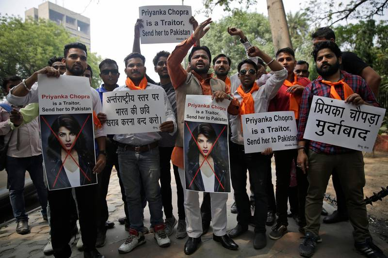 """Activists of ultra right-wing Hindu Sena or Hindu Army hold posters featuring photographs of Indian actress Priyanka Chopra during a protest in New Delhi, India, Saturday, June 9, 2018. U.S. television studio ABC on Friday issued an apology after an episode of Quantico, which stars Chopra in a lead role, triggered outrage among its Indian audience. The plot of the episode showed Indian nationalists trying to frame Pakistan in a terror plot. The posters in Hindi, left, read """"Stop damaging the image of India at international level"""" and right """"Down with Priyanka Chopra"""". (AP Photo/Altaf Qadri)"""
