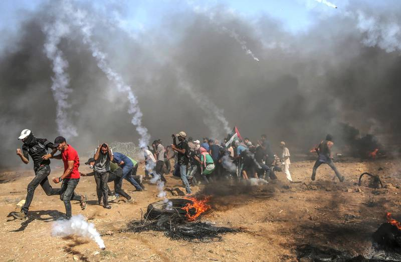 epa06795745 Palestinian protesters run for cover from Israeli tear-gas during clashes after Friday protests near the border east Gaza City, 08 June 2018 (issued 09 June 2018). Reports state that a twelve year old boy and other three Palestinians were killed and more than 600 protesters were wounded during the clashes near the border eastern Gaza Strip. Protesters plan to call for the right of Palestinian refugees across the Middle East to return to homes they fled in the war surrounding the 1948 creation of Israel.  EPA/MOHAMMED SABER