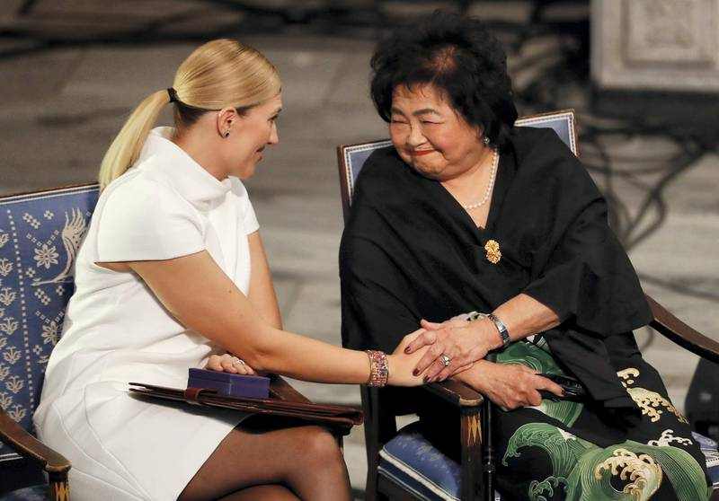 """Hiroshima nuclear bombing survivor Setsuko Thurlow (R) touches the hand of Beatrice Fihn, leader of ICAN (International Campaign to Abolish Nuclear Weapons) during the award ceremony of the 2017 Nobel Peace Prize at the city hall in Oslo, Norway, on December 10, 2017. The Nobel Peace Prize is awarded to the International Campaign to Abolish Nuclear Weapons (ICAN), as its representatives warn of """"an urgent threat"""" over US-North Korea tensions. / AFP PHOTO / Odd ANDERSEN"""