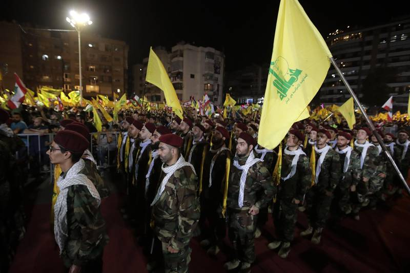 Fighters with the Lebanese Shiite Hezbollah party, carry flags as they parade in a southern suburb of the capital Beirut, to mark the al-Quds (Jerusalem) International Day, on May 31, 2019.  An initiative started by the late Iranian revolutionary leader Ayatollah Ruhollah Khomeini, Quds Day is held annually on the last Friday of the Muslim fasting month of Ramadan and calls for Jerusalem to be returned to the Palestinians. / AFP / Anwar AMRO