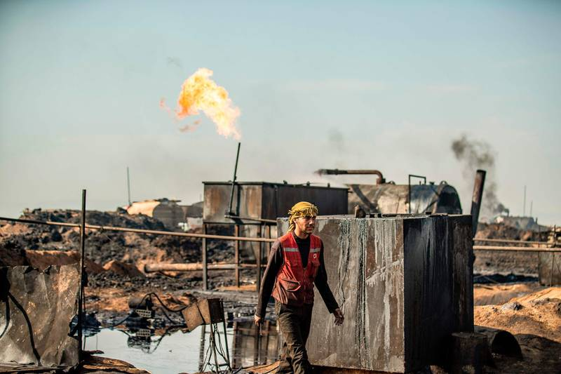 TOPSHOT - A Syrian worker walks at a primitive oil refinery in the countryside of al-Qahtaniyah town in Syria's northeastern Hasakeh province near the Turkish border, on March 11, 2020.  / AFP / Delil SOULEIMAN