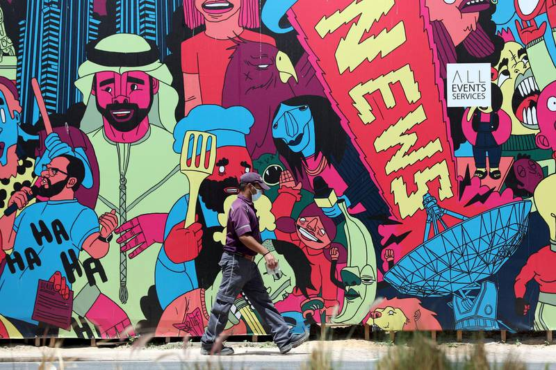 Dubai, United Arab Emirates - Reporter: N/A: Corona. A key worker wears a facemask as he walks passed a brightly coloured mural in Media City. Tuesday, April 14th, 2020. Dubai. Chris Whiteoak / The National