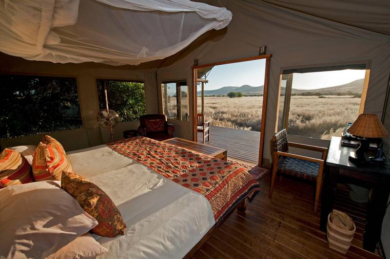 Desert Rhino Camp tent bedroom with view onto plains. Photo by Mike Myers
