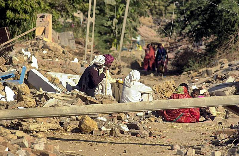 Homeless villagers wait for  relief in Bondh village in Bhuj district 28 January 2001 after their village was destroyed in an earthquake that struck north western India 26 January 2001, rendering thousands homeless. At least 15000 people are feared dead as a result of the tremor, with casualties expected to rise. AFP PHOTO/Arko DATTA (Photo by ARKO DATTA / AFP)