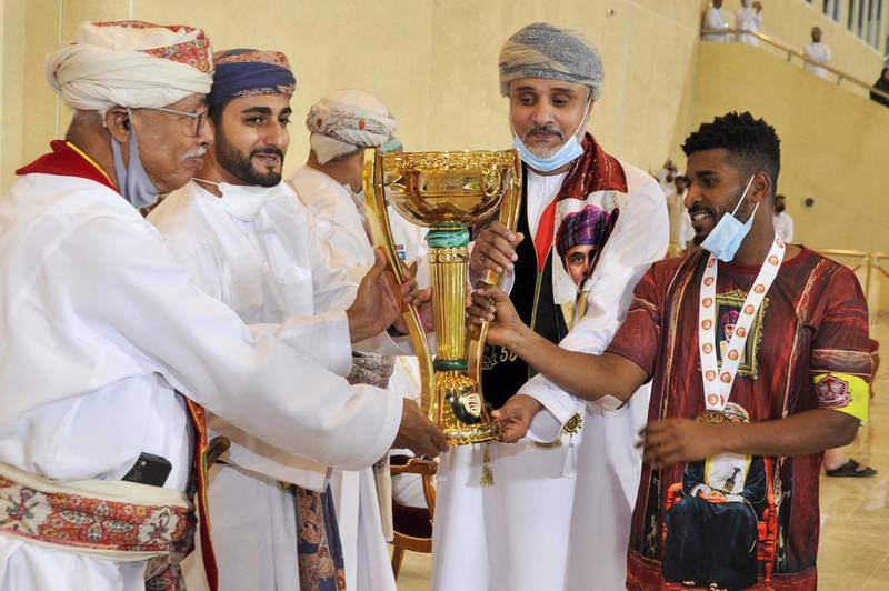 Omani Minister of Sport Sayyid Dhi Yazan bin Haitham (2nd-L) presents the trophy to Dhofar players after winning the Sultan Qaboos Cup final between Dhofar and Al-Orouba at the Rustaq Sports Complex west of the Omani capital Muscat on November 29, 2020. (Photo by Haitham AL-SHUKAIRI / AFP)