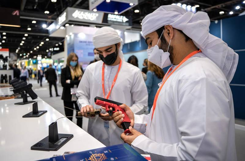 Abu Dhabi, United Arab Emirates, February 21, 2021.  Idex 2021, the first major in-person exhibition held in Abu Dhabi since the start of the Covid-19 pandemic, opened its doors to delegates on Sunday morning.  --Omar Al Matrooshi and Rashed Al Raess looks at a GLOCK 9mm. pistols.Victor Besa / The NationalSection:  NAReporter:  John Dennehy