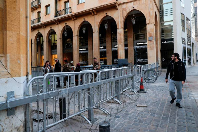 People walk past a metal barrier on a road leading to the Lebanese Parliament in the capital Beirut on December 18, 2019. Lebanon increased security around protest centres in central Beirut after several nights of violence last week disrupted two months of largely peaceful anti-government demonstrations. An officer who spoke to AFP on condition of anonymity said the barriers were intended to protect demonstrators from attacks. / AFP / ANWAR AMRO
