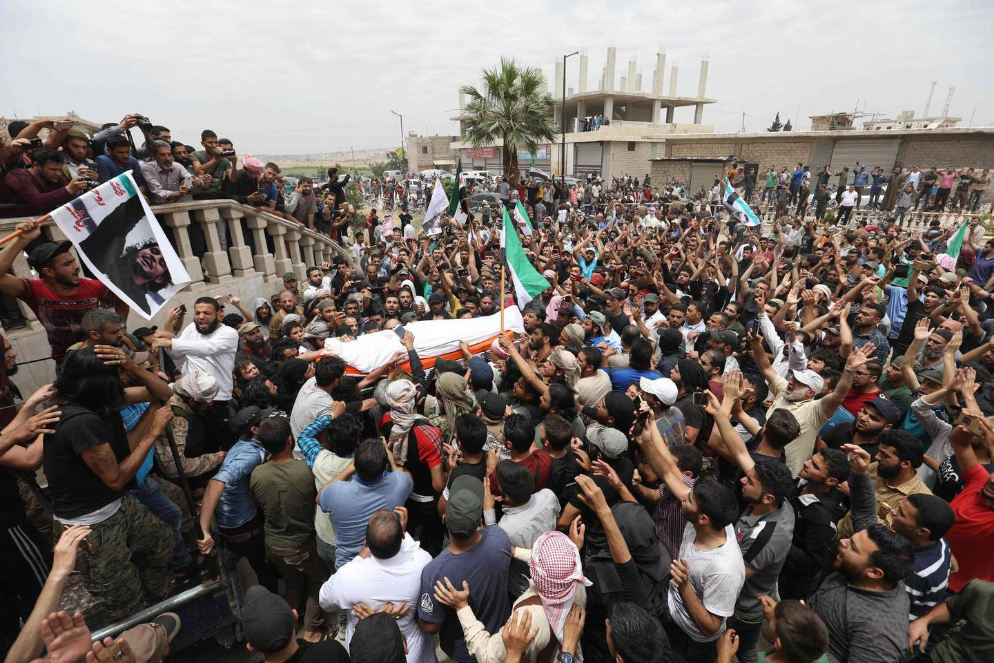 TOPSHOT - A picture taken on June 9, 2019 shows Syrians waving rebel flags and portraits of Abdel-Basset al-Sarout during the funeral of the late rebel fighter in al-Dana in Syria's jihadist-controlled Idlib region, near the border with Turkey. The Syrian goalkeeper turned rebel fighter who starred in an award-winning documentary died on June 8 of wounds sustained fighting regime forces in northwestern Syria, his faction said. Sarout, 27, was among dozens of fighters killed since June 6 in clashes with regime forces on the edges of the Idlib region. / AFP / OMAR HAJ KADOUR