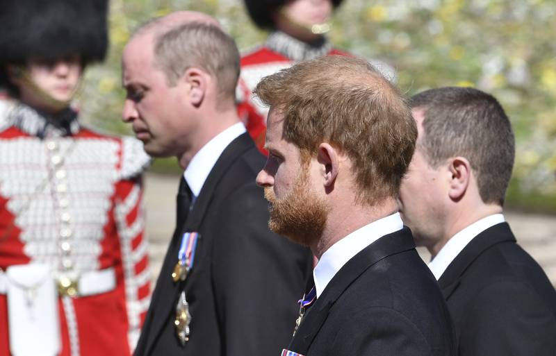 Prince William and Prince Harry follow the coffin during a procession arriving at St George's Chapel for the funeral of Britain's Prince Philip inside Windsor Castle in Windsor, England, Saturday, April 17, 2021. Prince Philip died April 9 at the age of 99 after 73 years of marriage to Britain's Queen Elizabeth II. (Mark Large/Pool via AP)