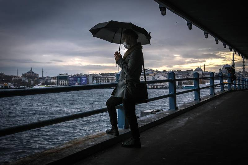 epa08910572 A man waits under the Galata Bridge with Hagia Sophia Mosque (L) and Yeni Mosque (R)  in the background on a rainy day, amid the ongoing coronavirus pandemic in Istanbul, Turkey, 28 December 2020. Turkey imposed curfews on weekdays after 9pm and full weekend lockdowns with the exception of tourists to combat the spread of coronavirus, after a recent spike in Covid-19 infections and related deaths.  EPA/SEDAT SUNA
