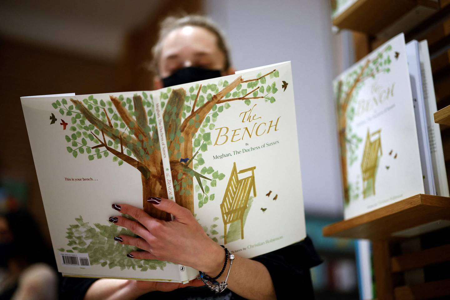 An employee poses with the children's book 'The Bench' by Meghan, Duchess of Sussex, which is inspired by her husband Harry and her son Archie, displayed in a bookshop in London on June 8, 2021, following its release.  / AFP / Tolga Akmen