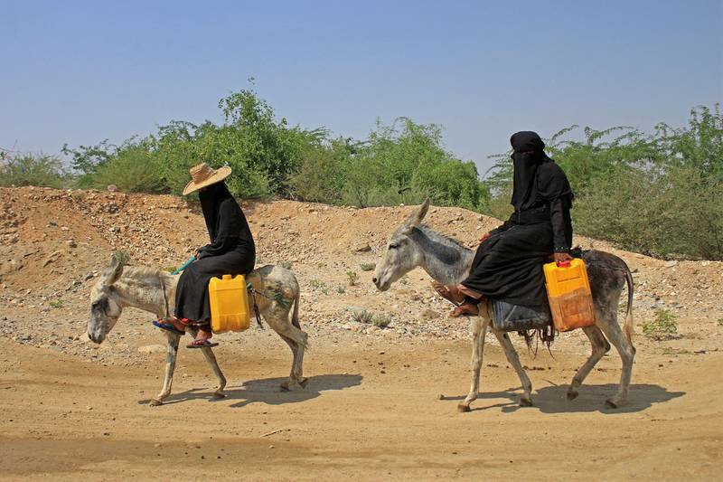 Yemeni women commute on donkeys carrying jerrycans of water at a camp for internally displaced people by conflict in the northern Hajjah province on October 12, 2020. (Photo by ESSA AHMED / AFP)