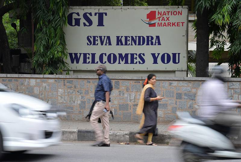 Pedestrians walk in front of a board advertising Goods and Service Tax (GST) in front of the Central Goods and Service Tax office in Bangalore on June 28, 2018.  / AFP / MANJUNATH KIRAN