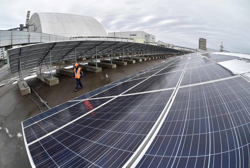 """A photo shows photovoltaic panels on the new one-megawatt power plant next to the New Safe Confinement over the fourth block of the Chernobyl nuclear plant on December 12, 2017. At ground zero of Ukraine's Chernobyl tragedy, workers in orange vests are busy erecting hundreds of dark-coloured panels as the country gets ready to launch its first solar plant to revive the abandoned territory. The new one-megawatt power plant is located just a hundred metres from the new """"sarcophagus"""", a giant metal dome sealing the remains of the 1986 Chernobyl accident, the worst nuclear disaster in the world. """"This solar power plant can cover the needs of a medium-sized village"""", or about 2,000 flats, Yevgen Varyagin, the head of the Ukrainian-German company Solar Chernobyl which carried out the project, told AFP. / AFP PHOTO / Genya SAVILOV"""