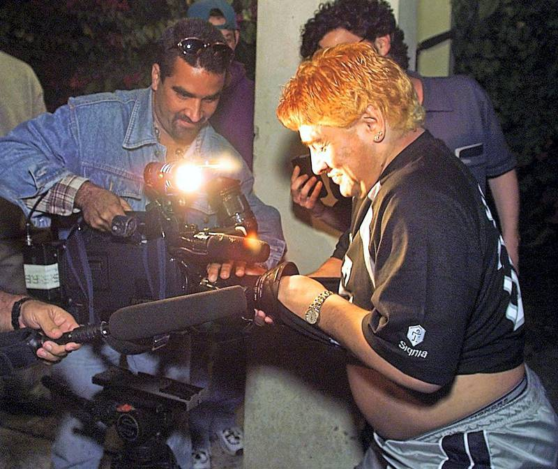 Argentinian football legend Diego Maradona (R) wipes the lens of a television camera during the celebration for his wife's birthday at a hotel in Havana 22 January, 2000.  Maradona is in undergoing a drug rehabilitation therapy at a clinic in Havana from his cocaine habit.   (ELECTRONIC IMAGE)   AFP PHOTO (Photo by ADALBERTO ROQUE / AFP)