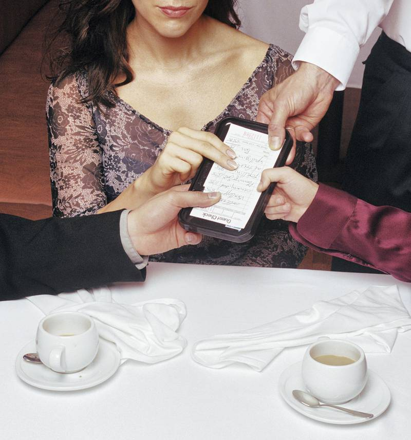 People at restaurant table with hands on check, mid section