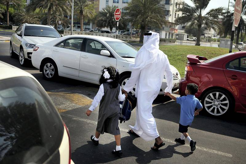 Abu Dhabi, United Arab Emitrates --- September 14, 2010 --- Parents keep their kids close as they navigate heavy traffic in front of GEMS American Academy-Abu Dhabi school. For the new school year, there will be increased traffic patrols at intersections and roads to ensure students' safety.    ( DELORES JOHNSON / The National )