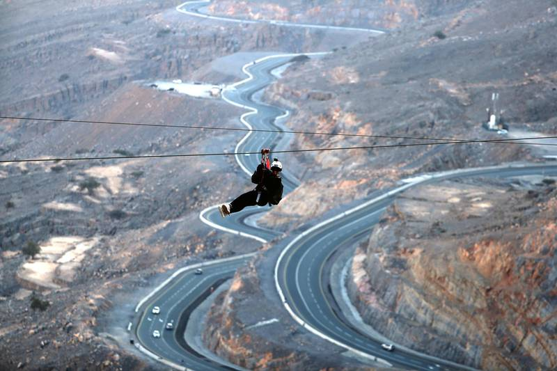 A picture taken on February 3, 2018, shows a woman riding the world's longest zip line, which measures almost 3 km in length, in Ras Al Khaimah in the United Arab Emirates. (Photo by KARIM SAHIB / AFP)
