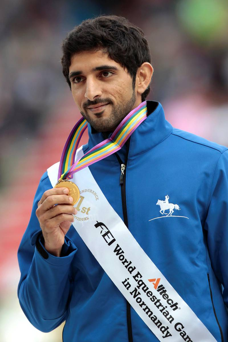 Gold medalist United Arab Emirate Sheikh Hamdan bin Mohamed al Maktoum 1er celebrates on August 29, 2014 on the podium during the medal ceremony of the Individual Endurance competition of the 2014 FEI World Equestrian Games, in the northwestern French city of Caen. AFP PHOTO /CHARLY TRIBALLEAU (Photo by CHARLY TRIBALLEAU / AFP)