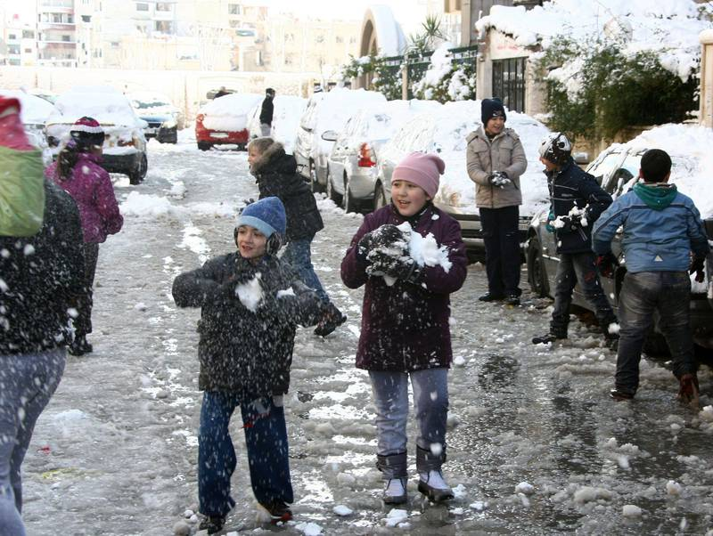 Children play with snow on January 10, 2013 in the Syrian capital of Damascus. Snow carpeted Syria's war-torn cities but sparked no let-up in the fighting, instead heaping fresh misery on a civilian population already enduring a chronic shortage of heating fuel and daily power cuts.  AFP PHOTO   / LOUAI BESHARA