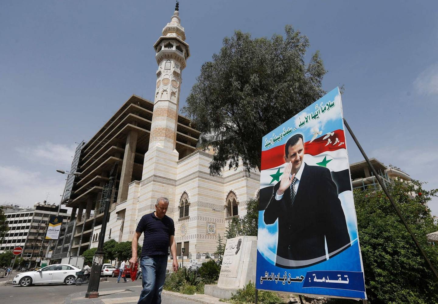 A Syria man walks past a giant portrait of President Bashar al-Assad at Marjeh square in the centre of capital Damascus on May 3, 2021. A Syrian former minister and a member of the Damascus-tolerated opposition will face Bashar al-Assad in this month's presidential election, the constitutional court said Monday. The Assad-appointed body approved only three out of 51 applications to stand in the May 26 ballot, among them the 55-year-old president himself,  / AFP / LOUAI BESHARA