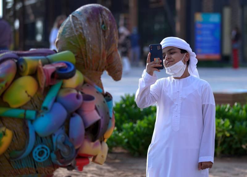 Abu Dhabi, United Arab Emirates, November 8, 2020.   The new Hudayriyat Leisure and Entertainment District at Hudayriyat Island.  A boy takes some photos of the many wildlife art works at the Marsana area.Victor Besa/The NationalSection:  NAReporter:  Haneen Dajani