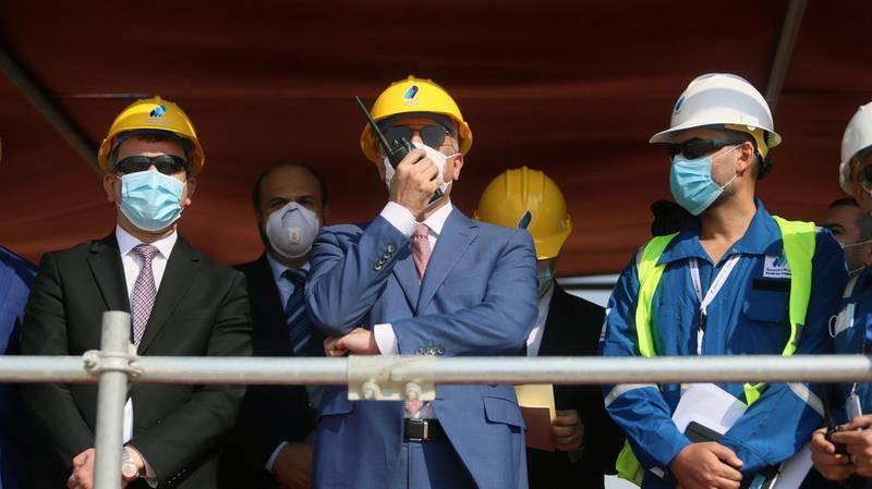 Iraq's Prime Minister Mustafa al-Kadhimi uses a walkie-talkie at the central station gas processing plant at Rumaila oilfield in Basra, Iraq, November 5, 2020. REUTERS/Essam Al-Sudani