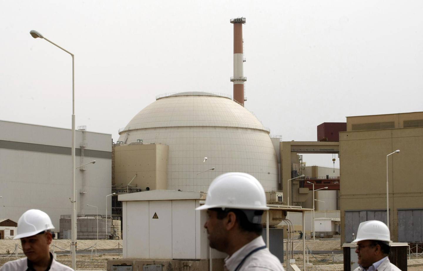 """(FILES) In this file photo taken on February 25, 2009 Iranian technicians walk outside the building housing the reactor of the Bushehr nuclear power plant, in the Iranian port town of Bushehr, 1200 kms south of Tehran. Iran will no longer respect limits it agreed on its enriched uranium and heavy water stocks under a 2015 nuclear deal with major powers, officials said on May 8, 2019. Iran's Supreme National Security Council said the measure was necessary to """"secure its rights and bring back balance"""" after Washington's abandonment of the agreement exactly one year ago on May 8, 2018. / AFP / AFP FILES / Behrouz MEHRI"""