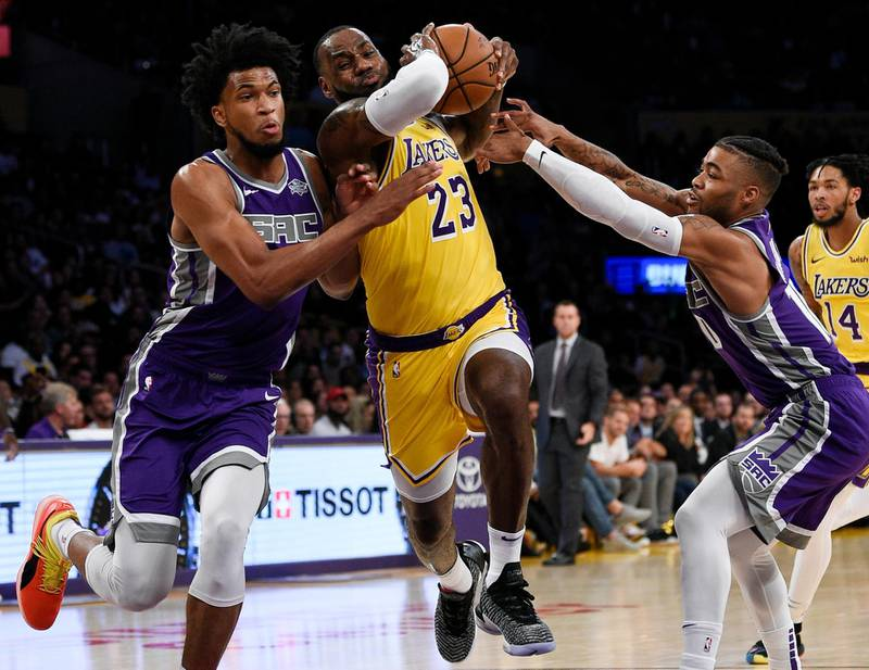 Los Angeles Lakers forward LeBron James, center, drives the ball between Sacramento Kings forward Marvin Bagley III, left, and guard Frank Mason III during the first half of an NBA preseason basketball game in Los Angeles, Thursday, Oct. 4, 2018. (AP Photo/Kelvin Kuo)