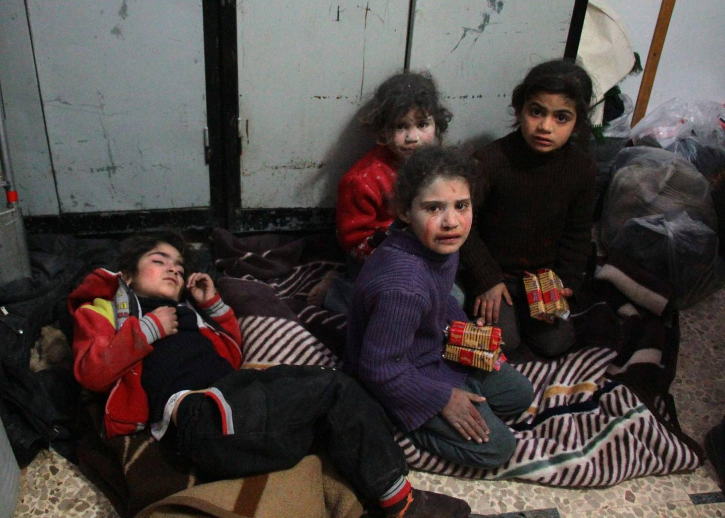 TOPSHOT - EDITORS NOTE: Graphic content / Syrian children cry at a make-shift hospital in Douma following air strikes on the Syrian village of Mesraba in the besieged Eastern Ghouta region on the outskirts of the capital Damascus, on February 19, 2018. Heavy Syrian bombardment killed dozens of civilians in rebel-held Eastern Ghouta, as regime forces appeared to prepare for an imminent ground assault. / AFP PHOTO / Hamza Al-Ajweh
