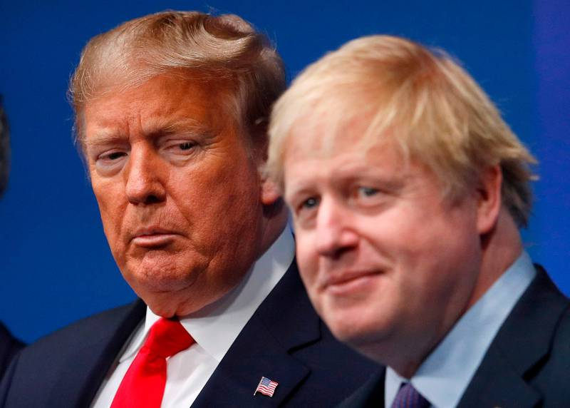 TOPSHOT - Britain's Prime Minister Boris Johnson (R) welcomes US President Donald Trump (L) to the NATO summit at the Grove hotel in Watford, northeast of London on December 4, 2019. / AFP / POOL / PETER NICHOLLS