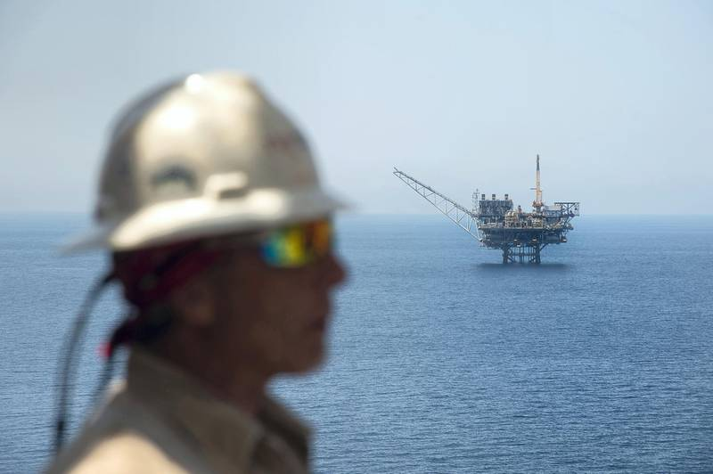 A picture taken on July 30, 2015 shows a worker from the Israeli gas-drill Tamar platform in front of the Mari-B platform in the Mediterranean Sea off the coast of Israel. The Tamar platform is located south-west off Tel Aviv, and some 150 kilometres south of the actual reservoir, from which it receives the gas via an underwater pipeline, before processing it. Israeli Prime Minister Benjamin Netanyahu announced on August 13, 2015 a major deal between his government and a consortium including US firm Noble Energy on natural gas production in the Mediterranean Sea. AFP PHOTO / AHIKAM SERI (Photo by AHIKAM SERI / AFP)