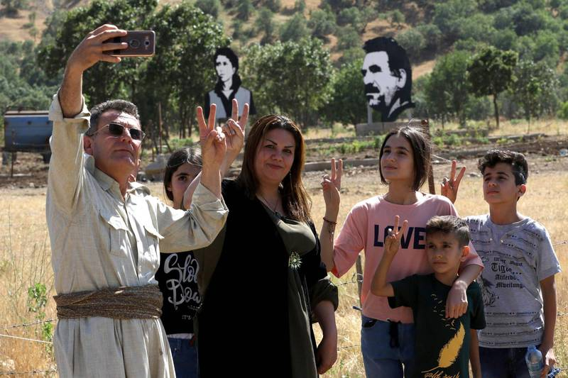 Iraqi Kurds pose for a selfie during a demonstration to protest a military operation by the Turkish army against the Kurdistan Workers' Party (PKK) in the Qandil Mountain, the PKK headquarters in northern Iraq, on June 22, 2018. Hundreds of Iraqi Kurds marched Friday to protest Turkish strikes against the Kurdistan Workers' Party (PKK) after Turkey's President Recep Tayyip Erdogan said Ankara would press an operation against its bases. / AFP / SAFIN HAMED