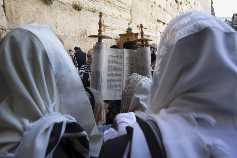 Jewish worshippers reads from the Torah scroll during a special priestly blessing for Passover at the Western Wall, Judaism's holiest prayer site, in Jerusalem's Old City April 6, 2015. REUTERS/Ronen Zvulun  - GF10000050823