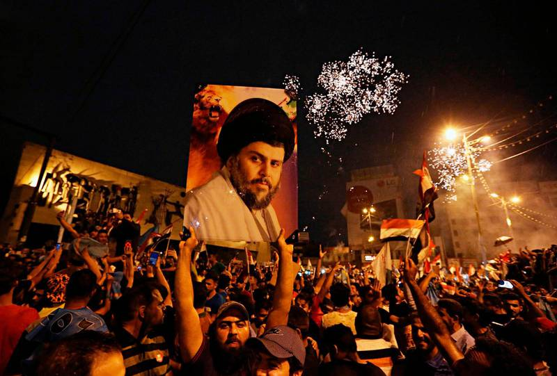 FILE - In this Monday, May 14, 2018 file photo, supporters of Shiite cleric Muqtada al-Sadr, carry his image as they celebrate in Tahrir Square, Baghdad, Iraq. Al-Sadr, who led punishing attacks on American forces after the 2003 U.S.-led overthrow of Saddam Hussein, appears set to secure the most significant victory of his political career with a strong showing in the May 12 parliamentary election. Al-Sadr gained popularity as a nationalist voice campaigning against corruption and against Iran's influence in the country. (AP Photo/Hadi Mizban)