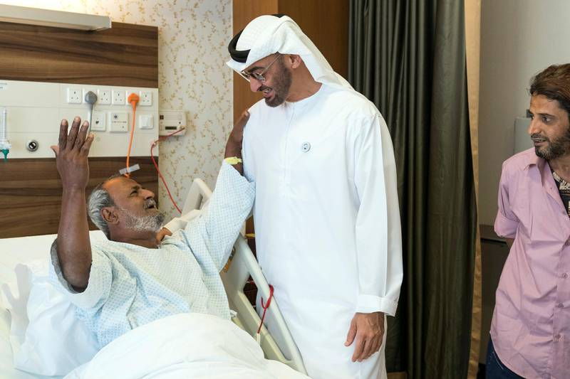 ABU DHABI, UNITED ARAB EMIRATES -  March 11, 2018: HH Sheikh Mohamed bin Zayed Al Nahyan, Crown Prince of Abu Dhabi and Deputy Supreme Commander of the UAE Armed Forces (2nd L), listens to a poem, while visiting Fadel Mahmoud Saleh (L), who is in Abu Dhabi receiving medical assistance at Burjeel Hospital.  ( Ryan Carter for the Crown Prince Court - Abu Dhabi ) ---