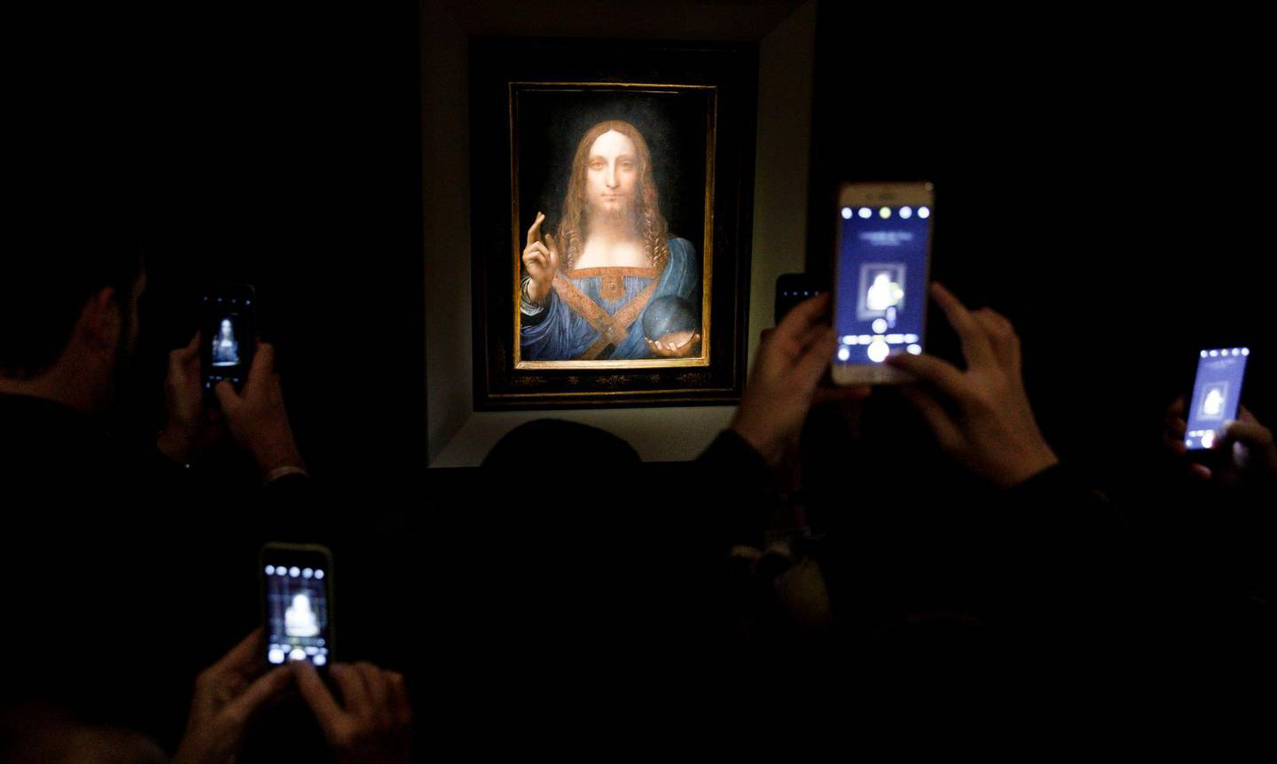 epa06382744 YEARENDER 2017 NOVEMBER  People take pictures of the painting 'Salvator Mundi' by Leonardo da Vinci (circa 1500) during a public preview before an auctioning of the painting tonight at Christie's auction house in New York, New York, USA, 15 November 2017. The painting is reportedly one of only twenty paintings by Da Vinci and was sold for 450 million USD.  EPA/JUSTIN LANE