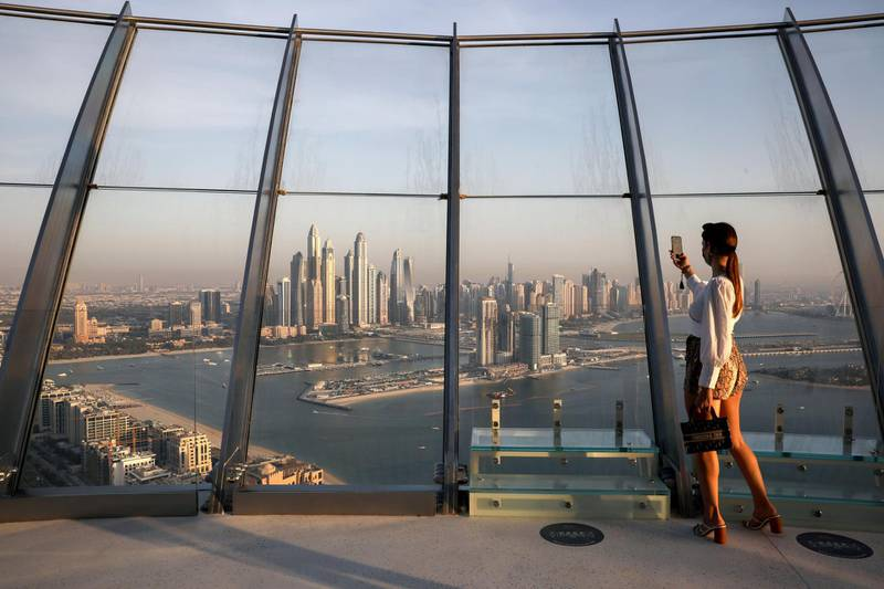 A woman takes a picture with a smartphone of the upscale Marina district from the Palm Tower in Dubai, United Arab Emirates, June 9, 2021. Picture taken June 9, 2021. REUTERS/Christopher Pike