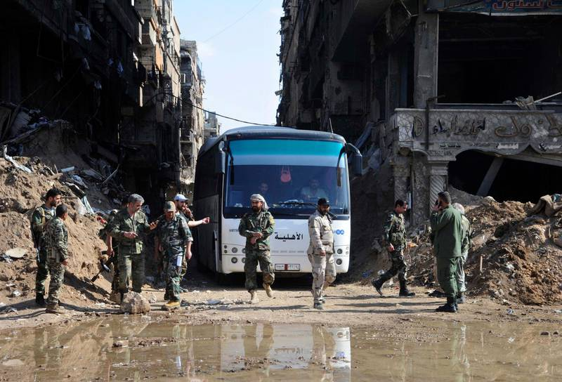 """FILE - In this file photo released April 30, 2018 by the Syrian official news agency, SANA, Syrian government forces oversee a bus carrying al-Qaida-linked fighters during an evacuation from the Palestinian refugee camp of Yarmouk, near Damascus, Syria. Syria's military said Monday, May 21, 2018, that it has liberated the last neighborhoods in southern Damascus held by the Islamic State including the Palestinian Yarmouk camp and Hajar al-Aswadand and declared the Syrian capital and its surroundings """"completely safe"""" and free of any militant presence. (SANA via AP, File)"""