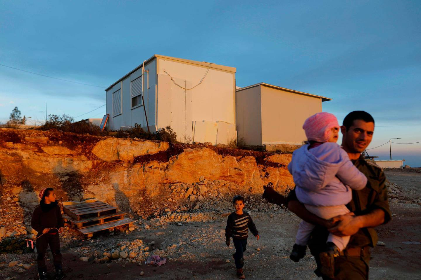 Men and children play in the Kida outpost near the Israeli Shilo settlement on January 27, 2020 near the Palestinian city of Nablus in the occupied West Bank. The Palestinians urged world powers to reject Donald Trump's peace plan, which they said president Mahmud Abbas had refused to discuss with his US counterpart despite several outreaches. Trump is due to unveil his proposal for Middle East peace this week in Washington, where he is scheduled to meet Israeli Prime Minister Benjamin Netanyahu and opposition leader Benny Gantz.  / AFP / MENAHEM KAHANA