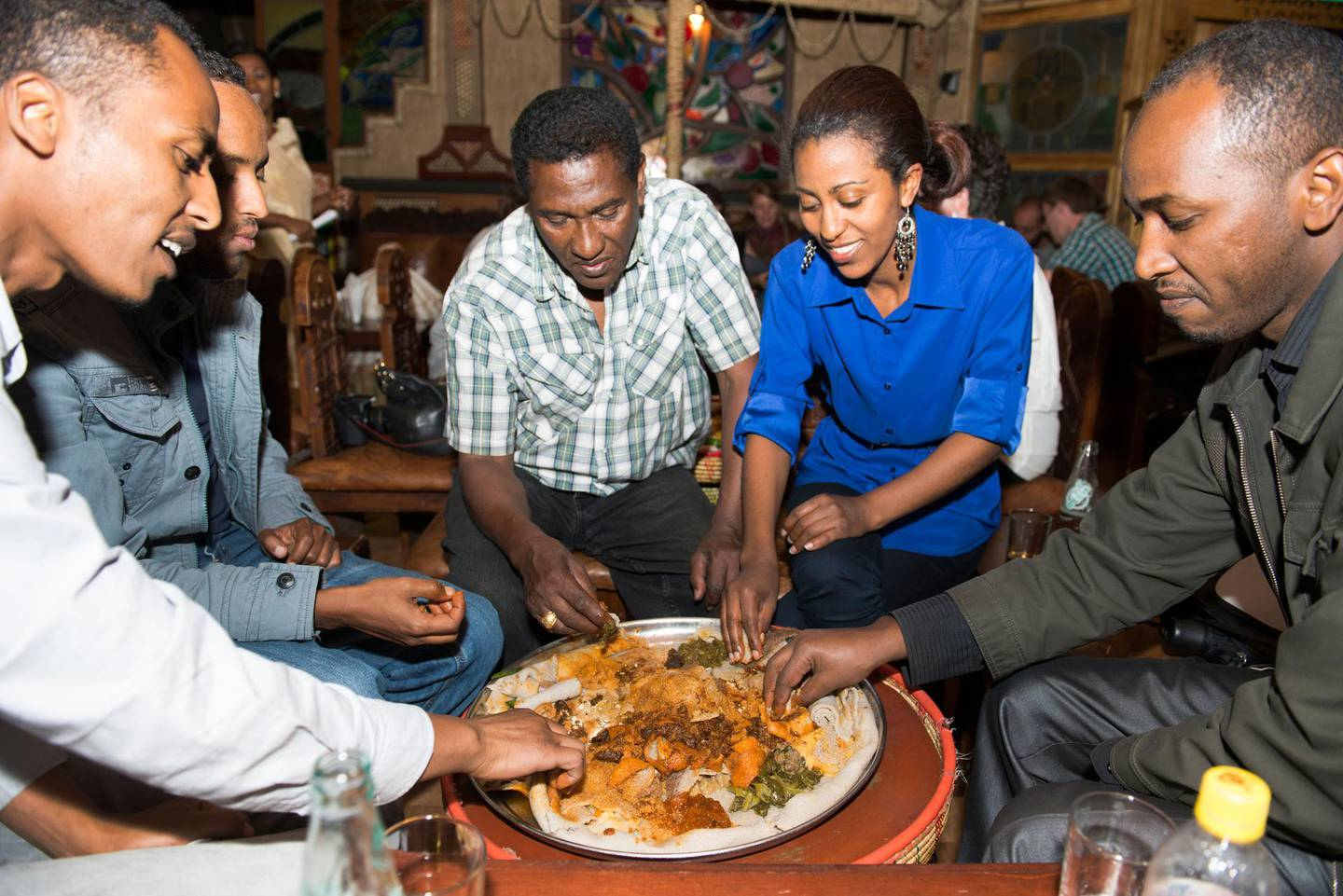 E0295E Ethiopians family and friends enjoy an Injera meal at the popular YOD Abyssinia Cultural Restaurant in Addis Ababa. Boaz Rottem / Alamy Stock Photo