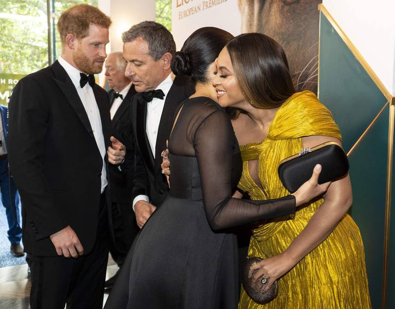 Britain's Prince Harry, Duke of Sussex (L) chats with Disney CEO Robert Iger as Britain's Meghan, Duchess of Sussex (2nd R) embraces US singer-songwriter Beyoncé (R) as they attend the European premiere of the film The Lion King in London on July 14, 2019.  / AFP / POOL / Niklas HALLE'N