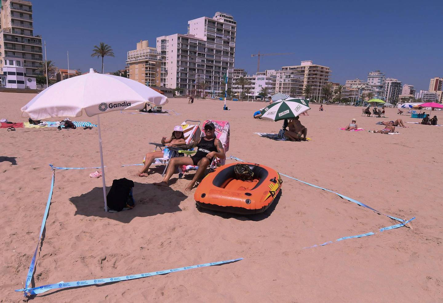 (FILES) In this file photo taken on July 01, 2020 People use a barrier tape to set a secure social distance space at the Nord Beach in Gandia, near Valencia on July 1, 2020. Spain will allow all vaccinated travellers to visit the country from June 7, Prime Minister Pedro Sanchez said on May 21, 2021, as the tourism hotspot aims to revive its virus-battered travel industry. / AFP / JOSE JORDAN