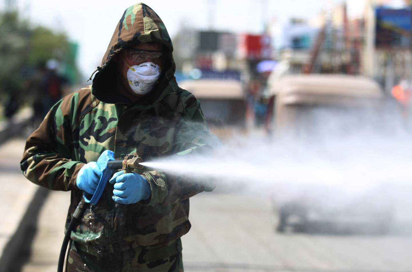 An Iraqi Civil Defence teams disinfects the streets of Sadr City in Baghdad on March 24, 2020 as a precaution against the coronavirus COVID-19 during the imposition of a curfew in Iraq. / AFP / AHMAD AL-RUBAYE