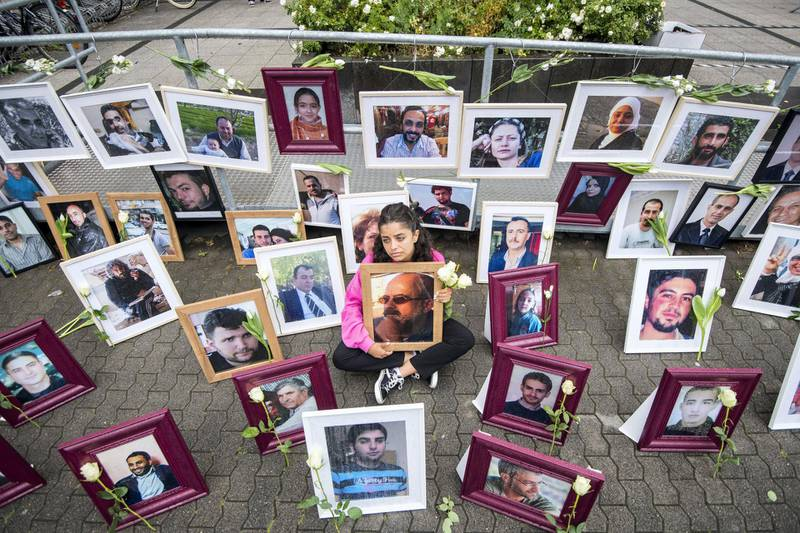 Syrian campaigner Wafa Mustafa sits between pictures of victims of the Syrian regime as she holds a picture of her father, during a protest outside the trial against two Syrian alleged former intelligence officers accused for crimes against humanity, in the first trial of its kind to emerge from the Syrian conflict, on June 4, 2020 in Koblenz, western Germany. - Wafa was part of the resistance against the Syrian government and had to flee Syria once her dad was arrested. She came to Germany in 2016. (Photo by Thomas Lohnes / AFP)